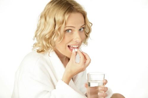 женщина принимает таблетки от глистов
