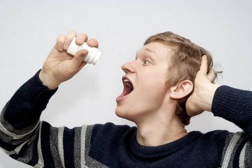 мужчина пьет таблетки от паразитов